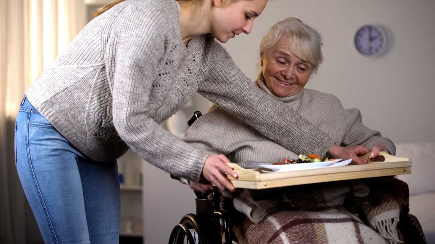 Arizona Family Caregiver providing a meal for an older women in a wheelchair