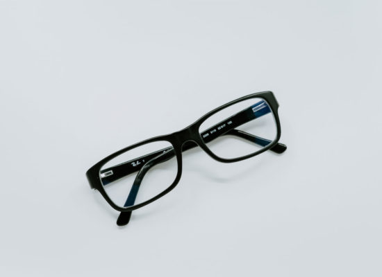 A black pair of Ray Ban glasses a person would wear to correct low vision.