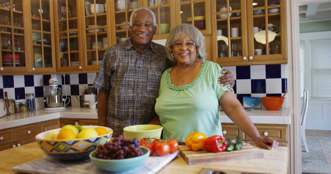 Two aging seniors in the kitchen, posing in front of an array of healthy foods.