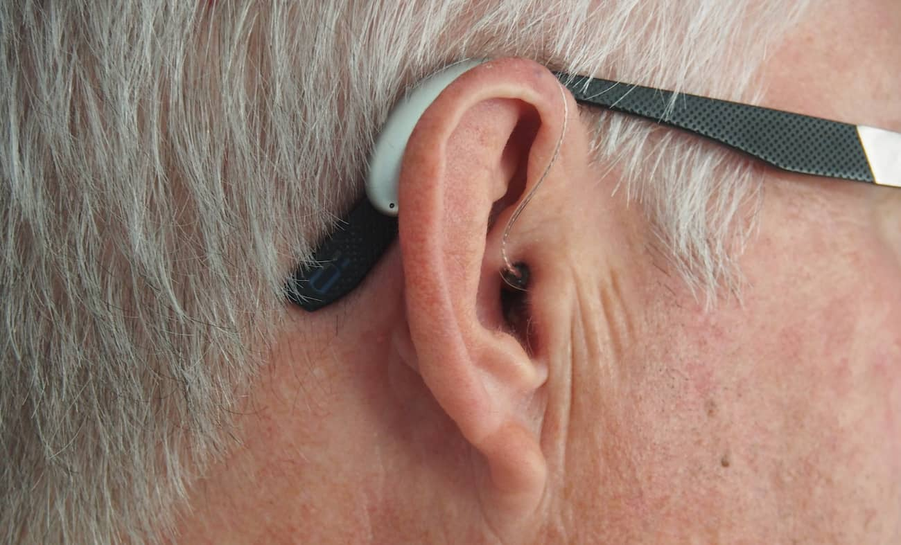 A close up of a man's hearing aid in his ear.