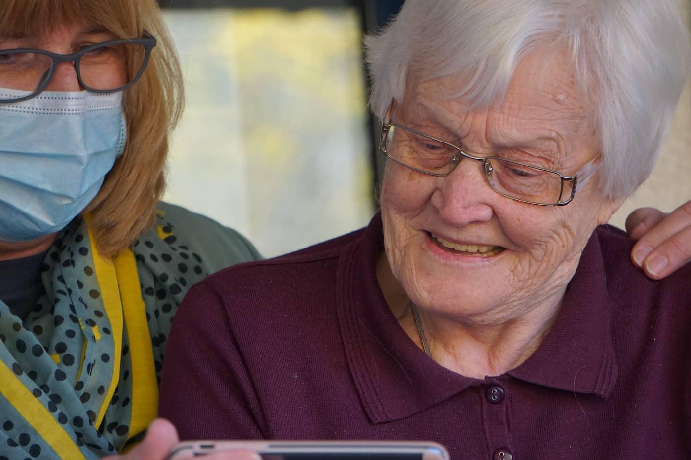 An informal caregiver helps an older women watch a video on an iPhone