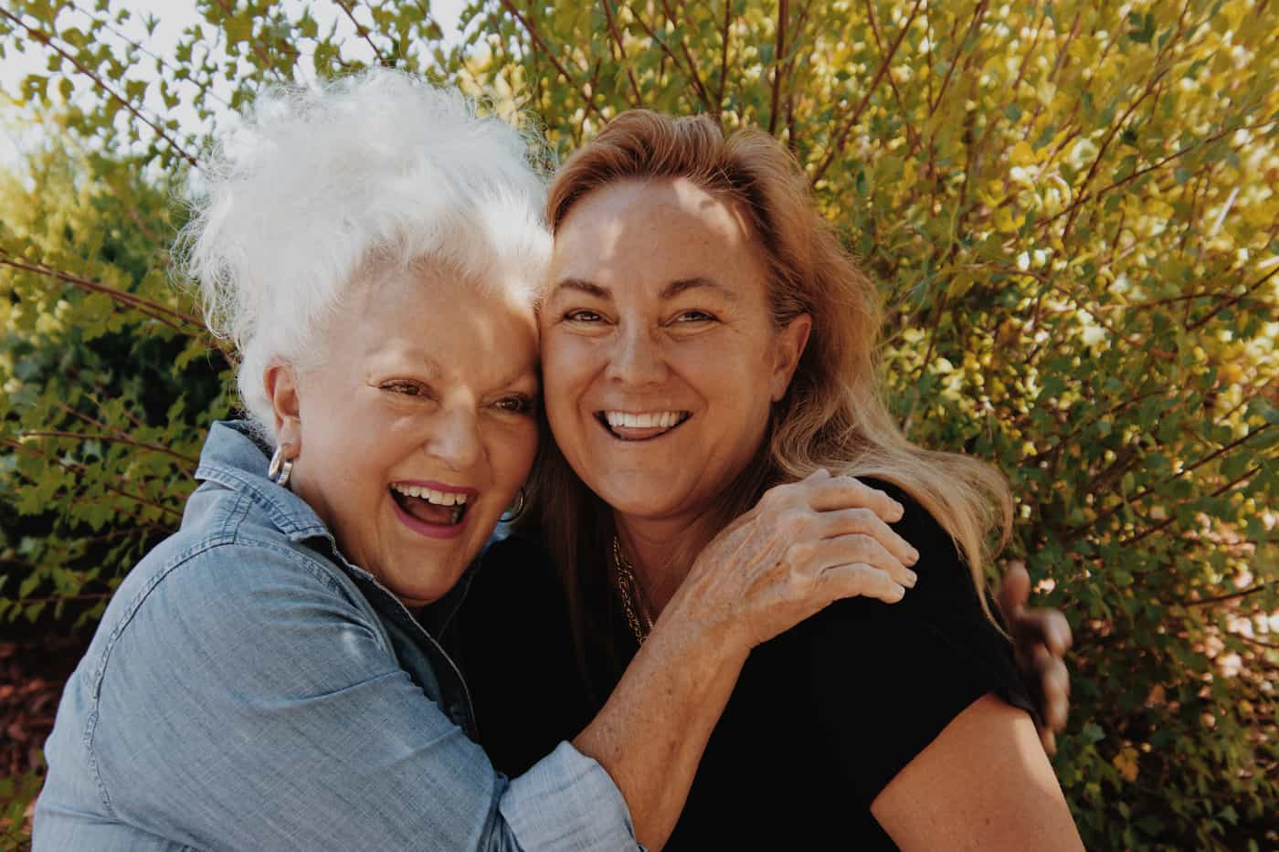 a woman talking to her senior mother about hiring a caregiver