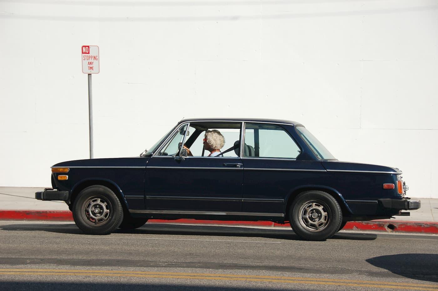 An older woman driving a vintage car.