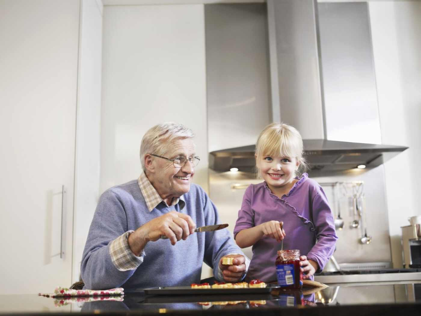 Senior avoiding malnutrition by preparing healthy food with a young girl.