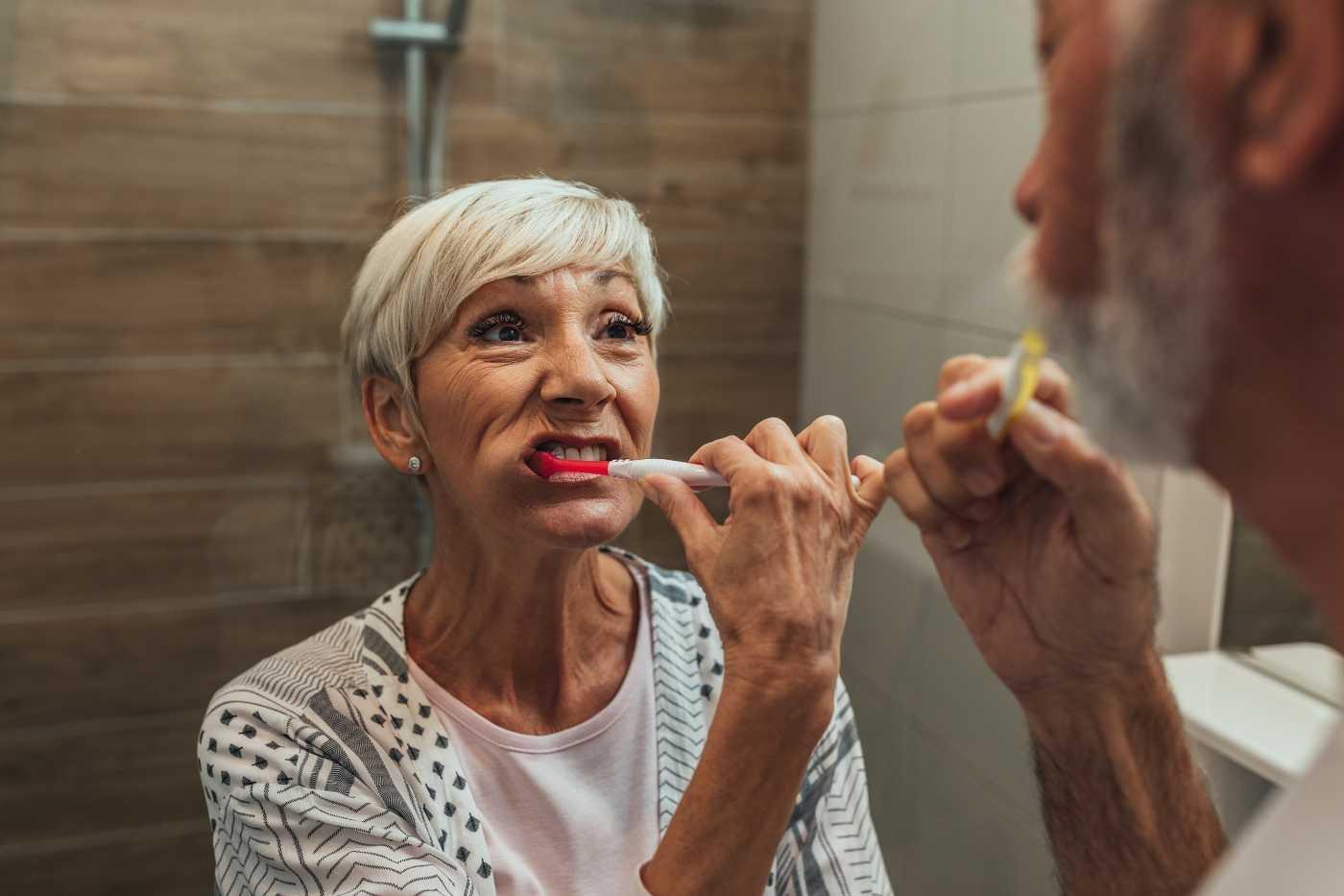Two older adults practicing good dental hygiene