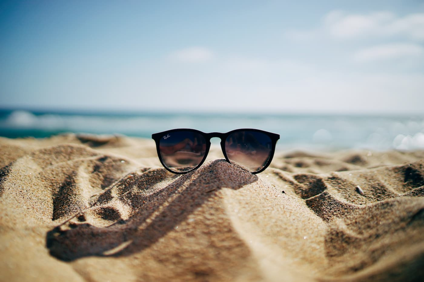 a pair of ray ban sunglasses on the beach in the summer sun