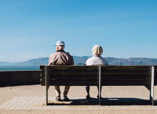 Two seniors sitting on a bench in front of the ocean during the COVID-19 pandemic